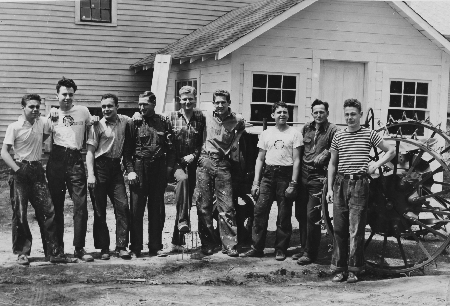 ": In 1941-42, student volunteer farmers posed in front of the Farmall tractor KUA had acquired that year. With them, are two of their leaders, 2nd from right, Assistant Headmaster Wilmot Babcock, of whom it was said, ""Scientific farming is his weakness …"" and maintenance worker Ray Cutts, 4th from left, of whom it was also said, he and ""Mrs. Ray Cutts, ... are the hardest-working, loyal people of which any institution in the state can boast."""